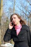 Una mujer en una capa negra que habla en un teléfono móvil Fotografía de archivo libre de regalías