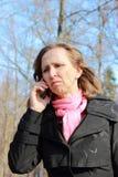 Una mujer en una capa negra que habla en un teléfono móvil Fotos de archivo libres de regalías