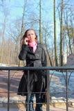 Una mujer en una capa negra que habla en un teléfono móvil Fotografía de archivo
