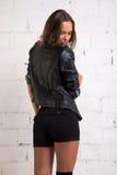 Una mujer en una chaqueta negra retrocede y mira el piso Pared de ladrillo blanca, no aislada Fotografía de archivo