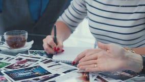 Una mujer en una chaqueta rayada que toma notas en un cuaderno durante una reunión de negocios almacen de metraje de vídeo