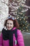 Una mujer en una chaqueta roja en un fondo de cerezas florecientes y del árbol de navidad Imagen de archivo libre de regalías