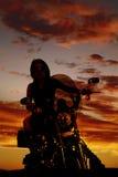 Una mujer en una motocicleta en la sentada de la puesta del sol Fotografía de archivo