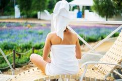 Una mujer en una toalla de baño se está sentando en un salón en una terraza Foto de archivo