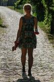Una mujer en vestido verde está caminando abajo de la colina descalzo en un pavimento, su sombra puede ser vista en los guijarros imagenes de archivo