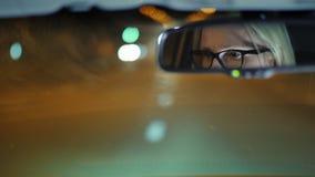 Una mujer en vidrios conduce un coche a través de la ciudad de la noche Su cara se refleja en el espejo retrovisor metrajes