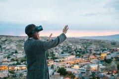 Una mujer en vidrios de la realidad virtual en el fondo de una puesta del sol sobre la ciudad Concepto de tecnologías futuras mod imágenes de archivo libres de regalías