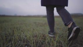 Una mujer en zapatillas de deporte y una capa va en la hierba mojada almacen de video