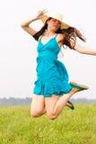 Una mujer encantadora salta en la naturaleza imagenes de archivo