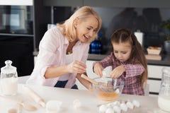 Una mujer enseña una muchacha a cómo hacer una galleta Muchacha asustada que azota los huevos Imagenes de archivo