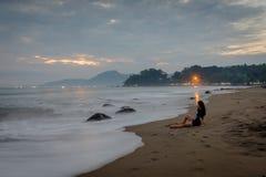 Una mujer es que sienta y que disfruta del momento en la playa de Karang Hawu, Java del oeste, Indonesia foto de archivo libre de regalías