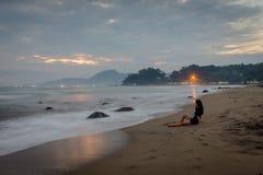 Una mujer es que sienta y que disfruta del momento en la playa de Karang Hawu, Java del oeste, Indonesia foto de archivo