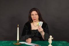 Una mujer es tarjetas de tarot de la lectura Fotos de archivo libres de regalías