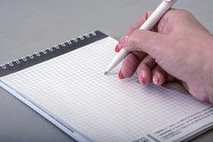 Una mujer escribe en un cuaderno con una pluma Imagen de archivo libre de regalías