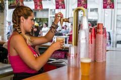 Una mujer española llena un vidrio de cerveza Imágenes de archivo libres de regalías