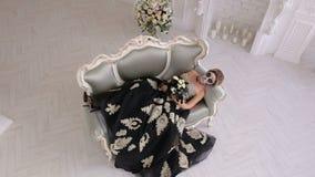 Una mujer espeluznante en un vestido y con maquillaje en forma de un cráneo miente en el sofá retro almacen de metraje de vídeo