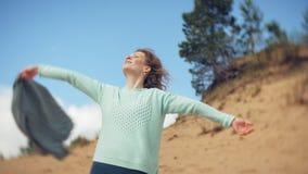 Una mujer está caminando a lo largo de la arena en la playa por el mar, disfrutando de vida almacen de video