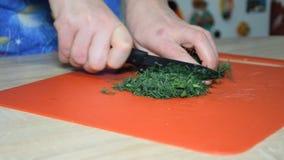 Una mujer está cortando el eneldo para una ensalada