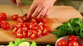 Una mujer está cortando los tomates de cereza para hacer una ensalada vegetal Primer almacen de video
