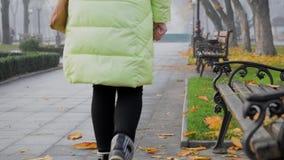 Una mujer está dejando en desorden en un césped Una persona lanza desperdicios en la calle almacen de metraje de vídeo