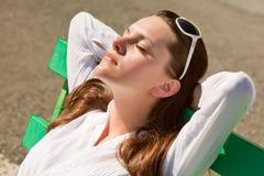 Una mujer está durmiendo en el banco Fotos de archivo