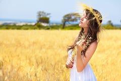 Una mujer está en el campo con una guirnalda Imagen de archivo