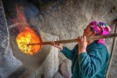 Una mujer está encendiendo un tandoor - un horno tradicional del Uzbek Foto de archivo