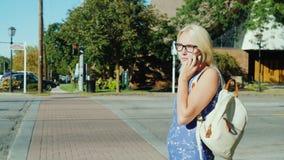 Una mujer está esperando una señal del semáforo de cruzar la calle El hablar en el teléfono metrajes