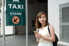 Una mujer está esperando un taxi Fotografía de archivo libre de regalías
