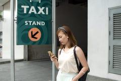 Una mujer está esperando un taxi Foto de archivo
