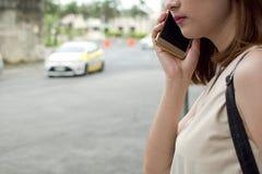 Una mujer está esperando un taxi Foto de archivo libre de regalías
