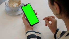 Una mujer está hablando con un amigo sobre una llamada video en un smartphone de la verde-pantalla almacen de metraje de vídeo