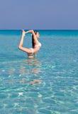 Una mujer está haciendo ejercicio de la flexibilidad en el mar Fotos de archivo libres de regalías