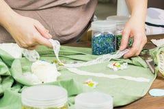 Una mujer está haciendo la joyería, un taller casero Manos femeninas que cr Foto de archivo