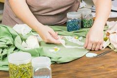 Una mujer está haciendo la joyería, un taller casero Manos femeninas que cr Fotografía de archivo libre de regalías