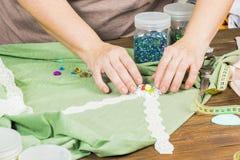 Una mujer está haciendo la joyería, un taller casero Manos femeninas que crean un accesorio con las gotas y las cintas Imágenes de archivo libres de regalías