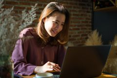 Una mujer está mecanografiando un mensaje en su ordenador portátil imagen de archivo libre de regalías