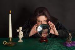 Una mujer está mirando en una bola cristalina Fotografía de archivo