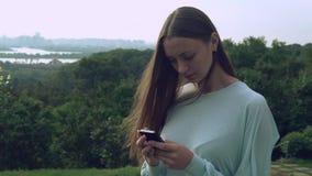 Una mujer está mirando su teléfono con su pelo que juega con el viento almacen de video