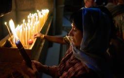Una mujer está mirando un manojo encendido de 33 velas fotos de archivo libres de regalías