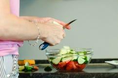 Una mujer está preparando una ensalada de verduras frescas imagenes de archivo