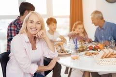 Una mujer está presentando en la tabla, después de lo cual su familia está comiendo Celebran día de la acción de gracias Imágenes de archivo libres de regalías