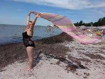 Una mujer está sosteniendo un pareo que se convierte en el viento Fotos de archivo