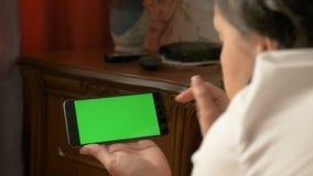 Una mujer está sosteniendo un smartphone con una pantalla verde mientras que miente en la cama almacen de metraje de vídeo