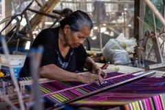 Una mujer está tejiendo telas coloridas tradicionales de Flores Todos los procesos que tejen utilizan el equipo manual y tradicio foto de archivo libre de regalías