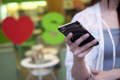 Una mujer está utilizando su teléfono Fotografía de archivo libre de regalías