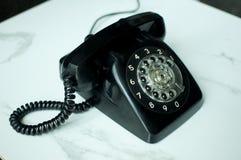 Una mujer está utilizando un teléfono del vintage Imagenes de archivo