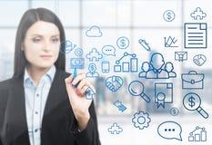 Una mujer está dibujando algunos iconos del negocio en la pantalla de cristal Oficina panorámica moderna con la opinión de Nueva  Imagen de archivo