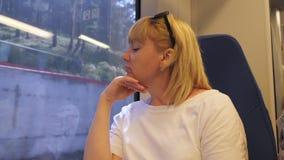 Una mujer est? viajando en tren La mujer que se sienta en el tren mira hacia fuera la ventana El concepto de turismo y de viaje almacen de video