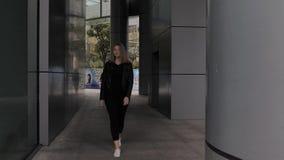 Una mujer europea joven camina a través de un arco del edificio moderno del negocio en centro de la ciudad almacen de metraje de vídeo